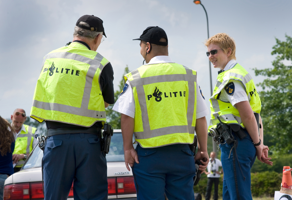 HAAKSBERGEN, NETHERLANDS - JUNE 09: Two policemen and a policewoman are talking with each other during a massive traffic control, june 09, 2011 in the Netherlands