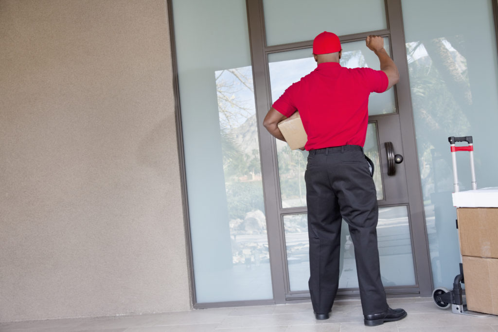 Delivery man knocking on a glass door