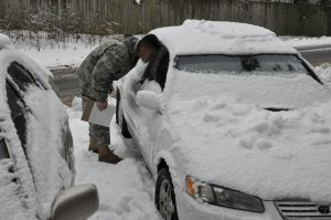 Soldier checks frozen vehicle for potential hypothermia casualties.